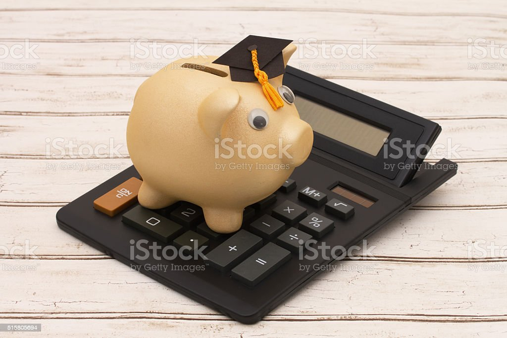 Golden piggy bank with grad cap and calculator on wood stock photo