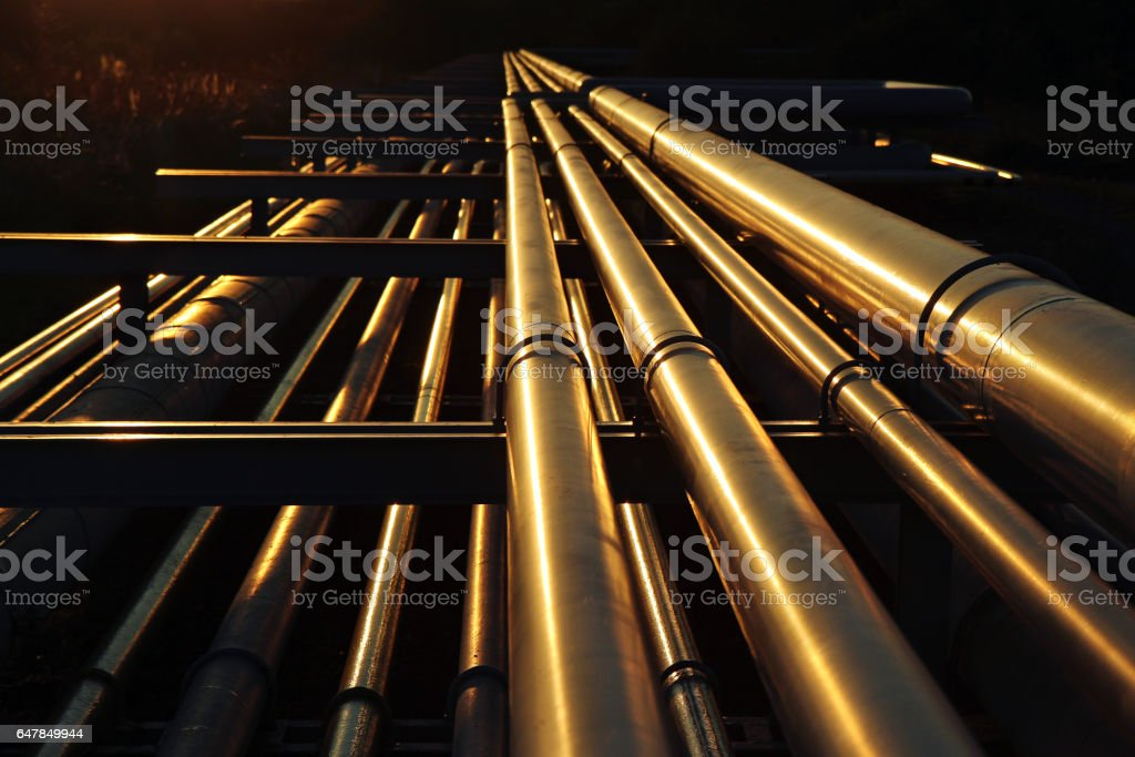 golden pipeline system transport in oil crude refinery stock photo