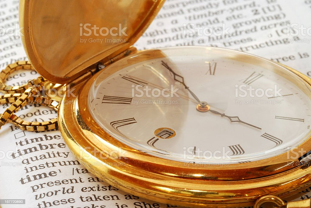 golden pocket watch on dictionary time royalty-free stock photo