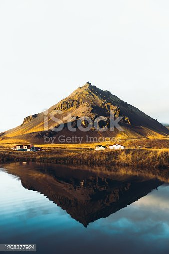 Scenic view if the beautiful triangle-shaped mountain, reflection lake and a small village during bright sunny day on the West Iceland