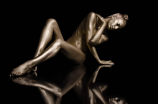 Golden Reflection Nude gold body painting on black background nude women pics stock pictures, royalty-free photos & images