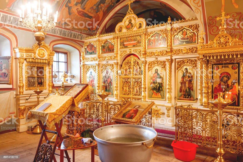 Golden religious utensils - Bible, cross, prayer book, missal, baptismal font. Interoior of Orthodox Christian Church. Russia. stock photo