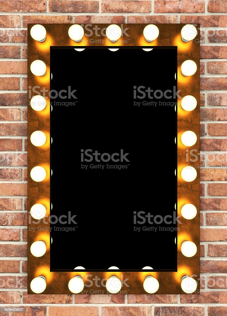 Golden retro makeup mirror on brick wall stock photo