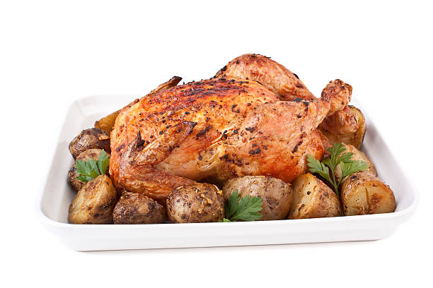 golden roasted chicken with potatoes stock photo