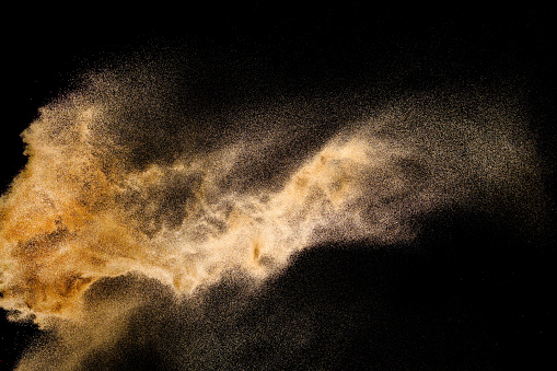 Golden sand explosion isolated on black background. Abstract sand cloud. Golden colored sand splash against dark background. Yellow sand fly wave in the air.