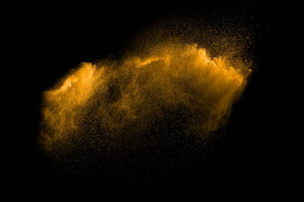 Explosion sable dorée isolée sur fond noir. Nuage de sable Résumé. Or splash de sable coloré sur fond sombre. Vague jaune phlébotome dans l'air. - Photo