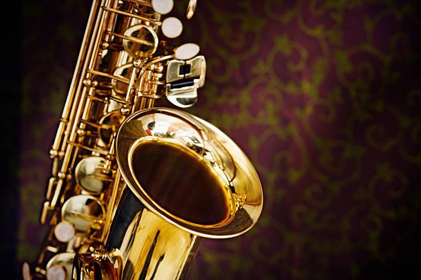 golden saxophone gleams contra un fondo de seda elegantemente decoradas incluyen - sur fotografías e imágenes de stock