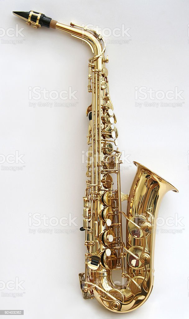 Golden saxophone lying sideways on blank surface stock photo
