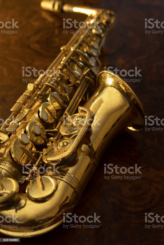 Golden saxophone on a wooden background stock photo