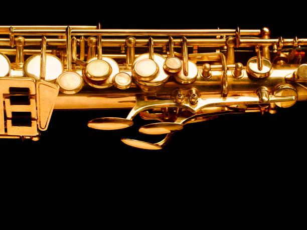 golden saxophon auf dunklem hintergrund - altsaxophon stock-fotos und bilder