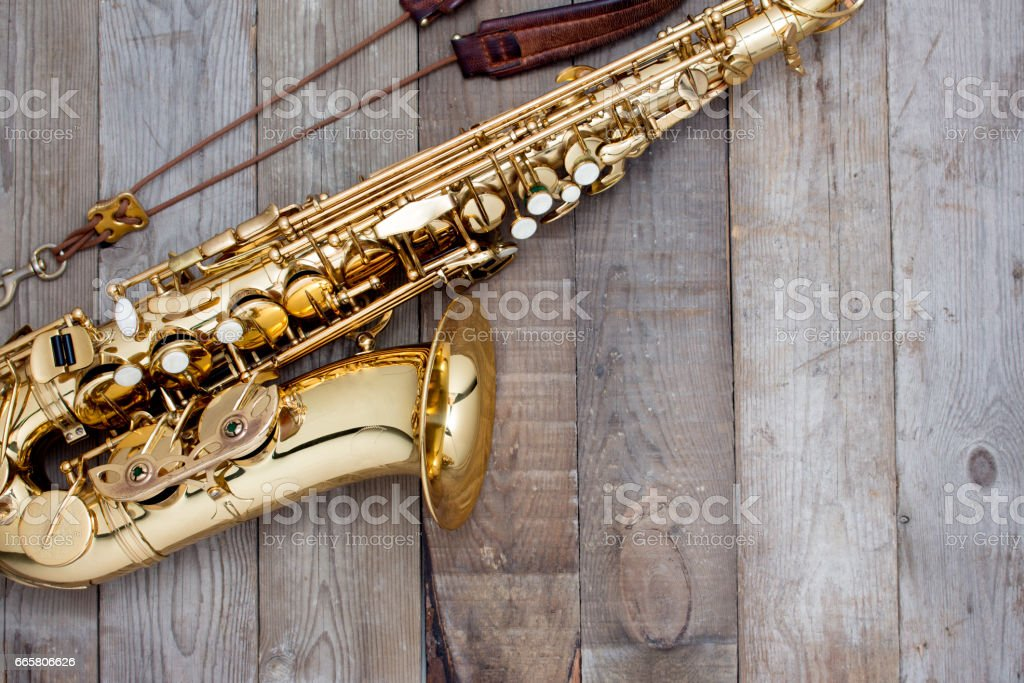 golden saxophone on table wooden background stock photo