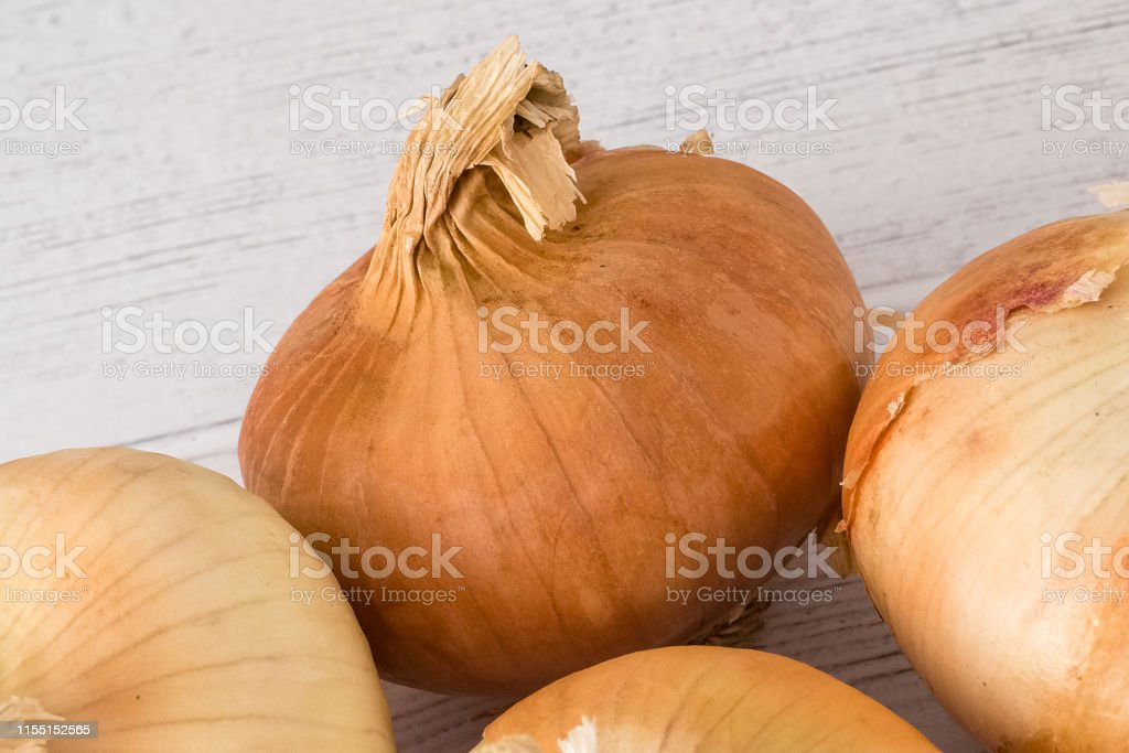 Four Golden Scottish Grown Onions on a white Wooden planked Board. A...