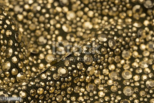512401542istockphoto golden sequins on texture textile selective focus 1134886681
