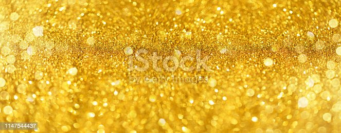 881350776 istock photo Golden shiny background, copy space for your Christmas greetings. Banner with defocused lights, bright yellow bokeh. Shimmer of gold glitter texture. Concept of New year, luxury holiday. 1147544437