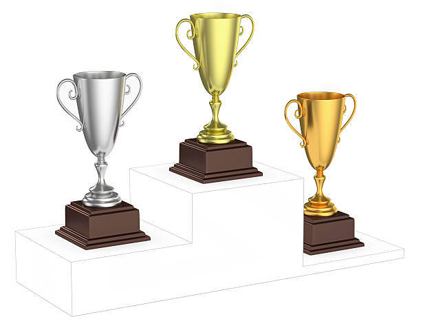 Golden, silver and bronze trophy cups on imaginary winners podiu stock photo