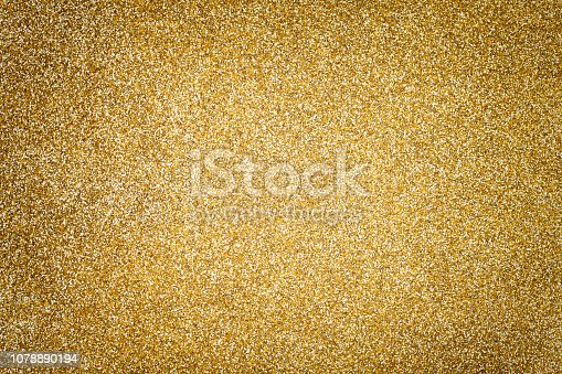 Golden sparkling background from small sequins, closeup. Brilliant shiny backdrop from textile. Shimmer yellow paper with vignette