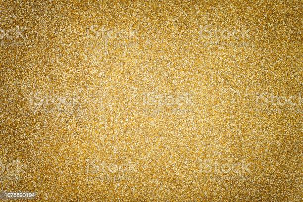 Photo of Golden sparkling background from small sequins, closeup. Brilliant backdrop.