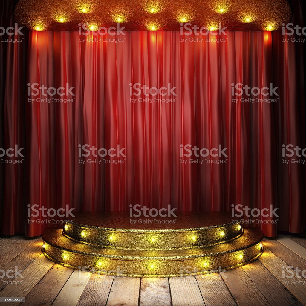 Golden stage with red curtain illuminated by spotlights stock photo