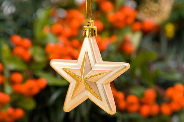 Golden Star Bauble in Front of Christmas Decoration stock photo