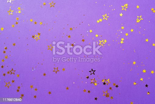istock Golden star sparkles on violet background. Christmas and New year concept. Festive backdrop with copy space 1176612840