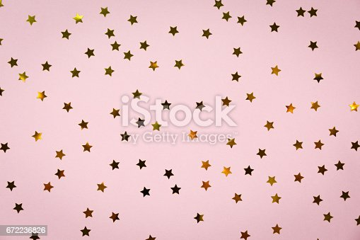 istock Golden star sprinkles on pink. Festive holiday background. Celebration concept 672236826