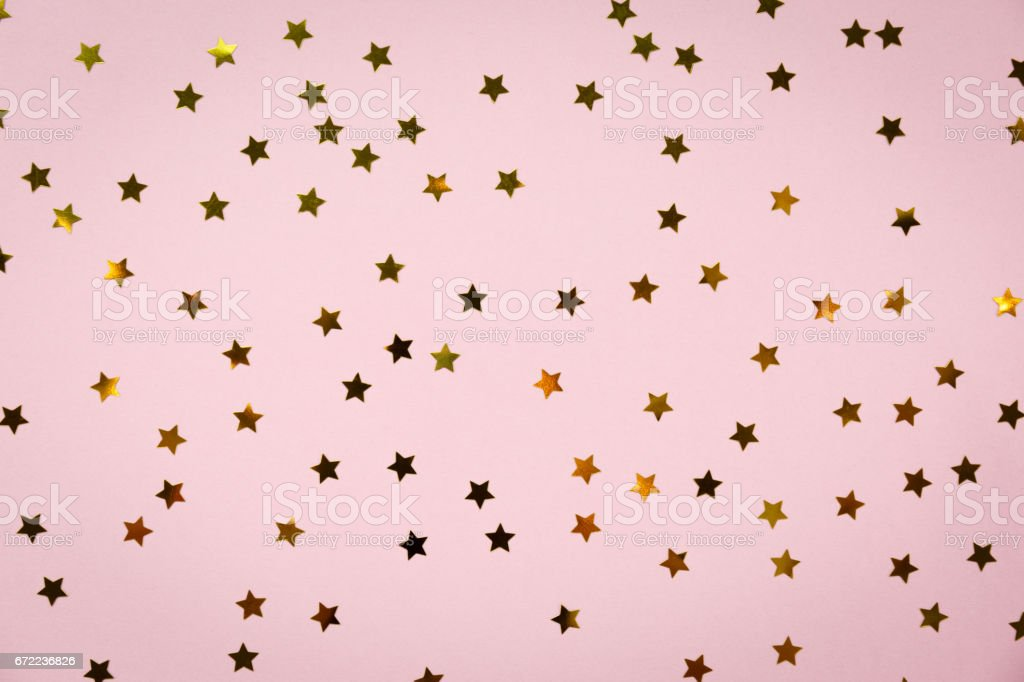 Golden star sprinkles on pink. Festive holiday background. Celebration concept stock photo