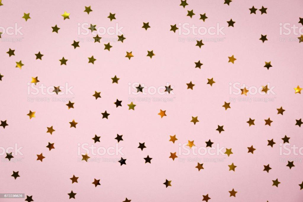 Chuviscos estrelas dourados na rosa. Fundo de feriado festivo. Conceito de celebração - foto de acervo