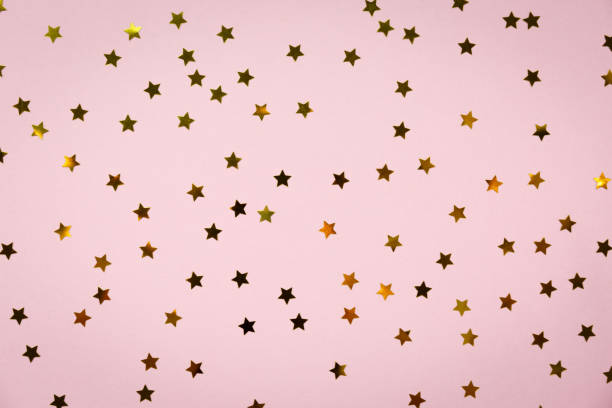 golden star sprinkles on pink. festive holiday background. celebration concept - star shape stock photos and pictures