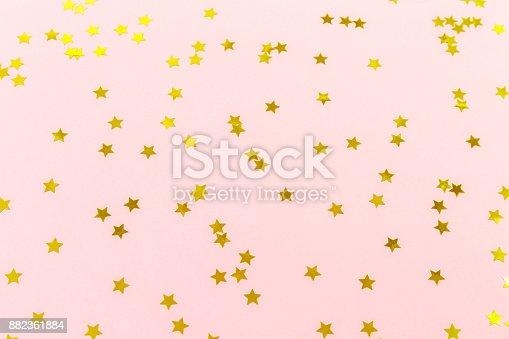 1040055260istockphoto Golden star sprinkles on pink. Festive holiday background. Celebration concept 882361884