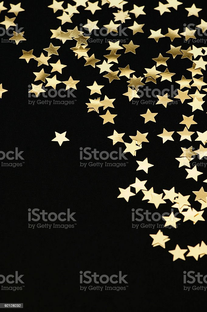 Golden stars falling from the top on black background stock photo