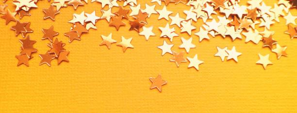 Golden stars glitter on orange paper background picture id1167293444?b=1&k=6&m=1167293444&s=612x612&w=0&h=3dvgdtoxql9ru7i8a 2vhwgzha  4gwiqs  szjl1n8=