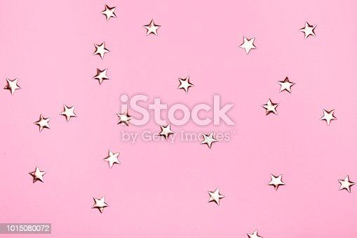 1040055260istockphoto Golden stars glitter on pink background. 1015080072