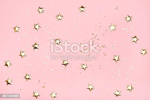 istock Golden stars glitter on pink background. 887494880