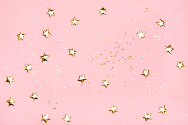 golden stars glitter on pink background. - star shape stock photos and pictures