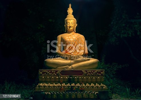 Golden statue of Buddha at a shrine in Wat Wisunarat temple, at night.