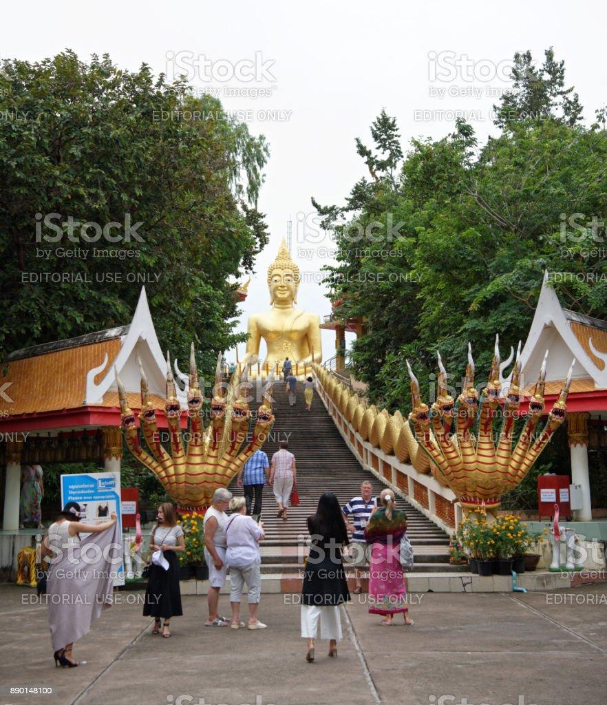 Golden Statue Of Buddha in Wat Phra Yai,The Big Buddha Temple At Pattaya.Tourists photograph, climb the stairs stock photo
