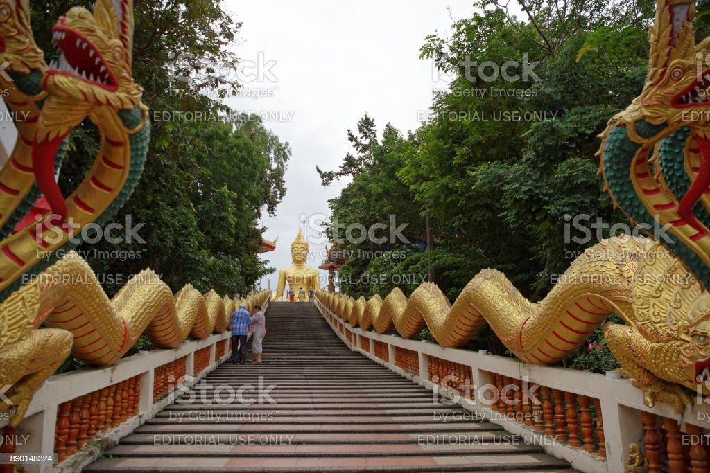 Golden Statue Of Buddha in Wat Phra Yai,The Big Buddha Temple At Pattaya.Tourists climb the stairs stock photo