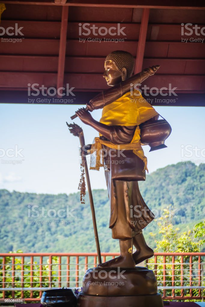 Golden statue of Phra Sivali, an arhat widely venerated among Theravada Buddhists. Sīvali is typically depicted standing upright and carrying a walking staff, an alms bowl and Buddhist prayer beads. zbiór zdjęć royalty-free