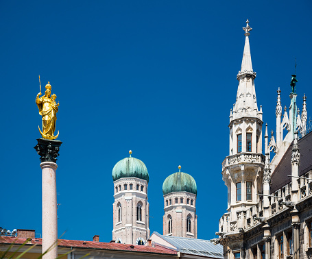 Golden statue of the Virgin Mary and tower in city center Munich