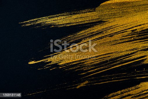 Golden strokes of acrylic paint with an art brush on a black background. Abstract background. Web banner.
