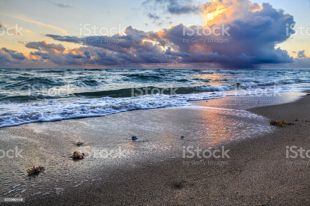 Golden sun rays beaming through the storm clouds over Atlantic stock photo