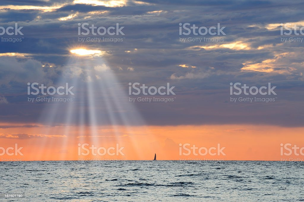 Golden sunbeam flowing over sailing ship and calm sea royalty-free stock photo