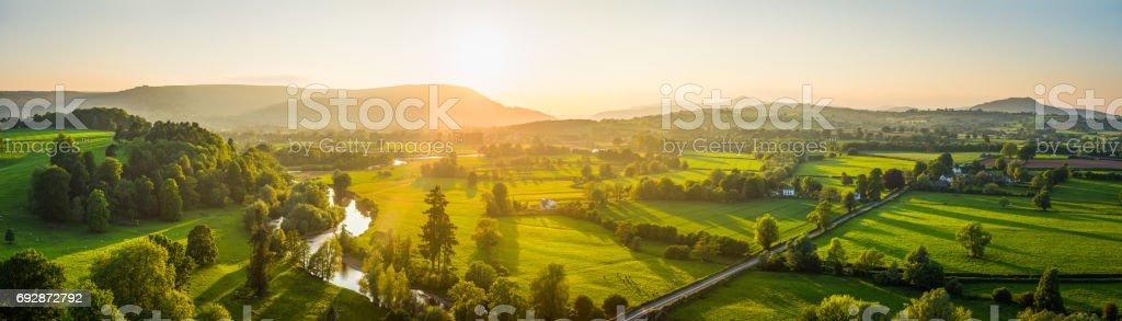 Golden sunlight illuminating idyllic river valley fields mountains aerial panorama stock photo