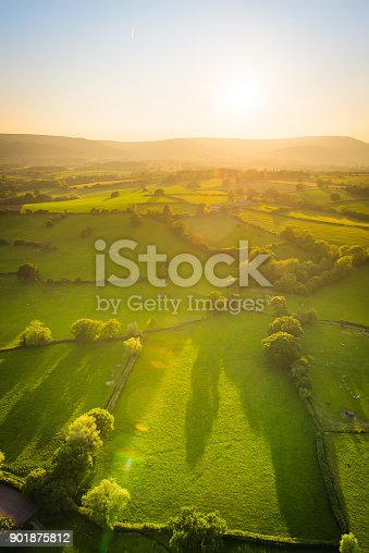 Aerial view across misty mountains and picturesque patchwork pasture illuminated by the warm glow of sunset.