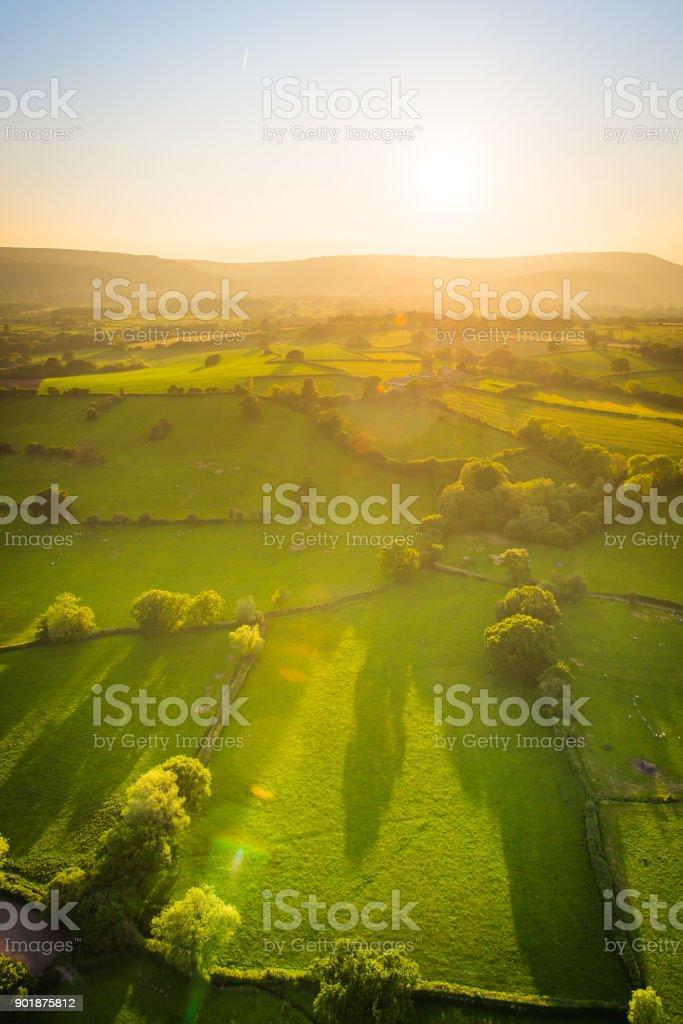 Golden sunlight illuminating idyllic rural landscape green pasture aerial photograph stock photo