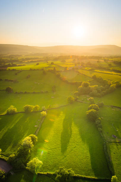 Golden sunlight illuminating idyllic rural landscape green pasture aerial photograph Aerial view across misty mountains and picturesque patchwork pasture illuminated by the warm glow of sunset. south wales stock pictures, royalty-free photos & images