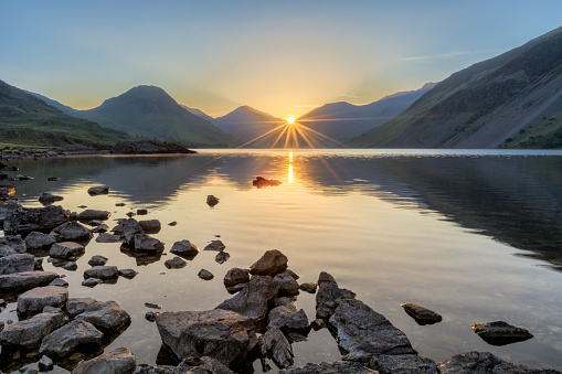Golden sunrise at Wastwater lake with rocks and mountains.