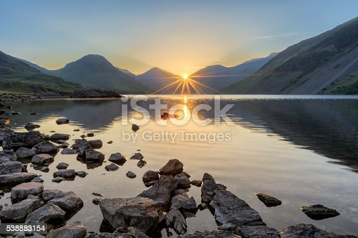 A photograph taken at Wastwater in the English Lake District on a fresh summer morning. The sun can be seen rising through the peaks of the mountains, creating a starburst sun ray effect.