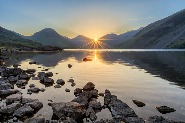 Golden sunrise at Wastwater lake with rocks and mountains. A photograph taken at Wastwater in the English Lake District on a fresh summer morning. The sun can be seen rising through the peaks of the mountains, creating a starburst sun ray effect. cumbria stock pictures, royalty-free photos & images