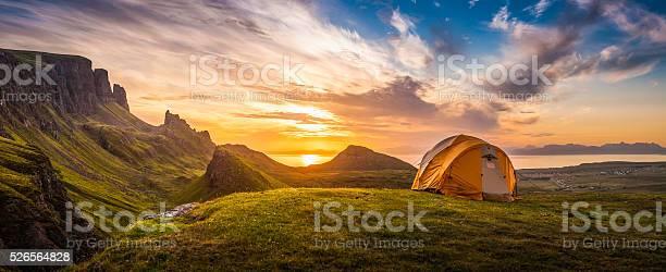 Photo of Golden sunrise illuminating tent camping dramatic mountain landscape panorama Scotland